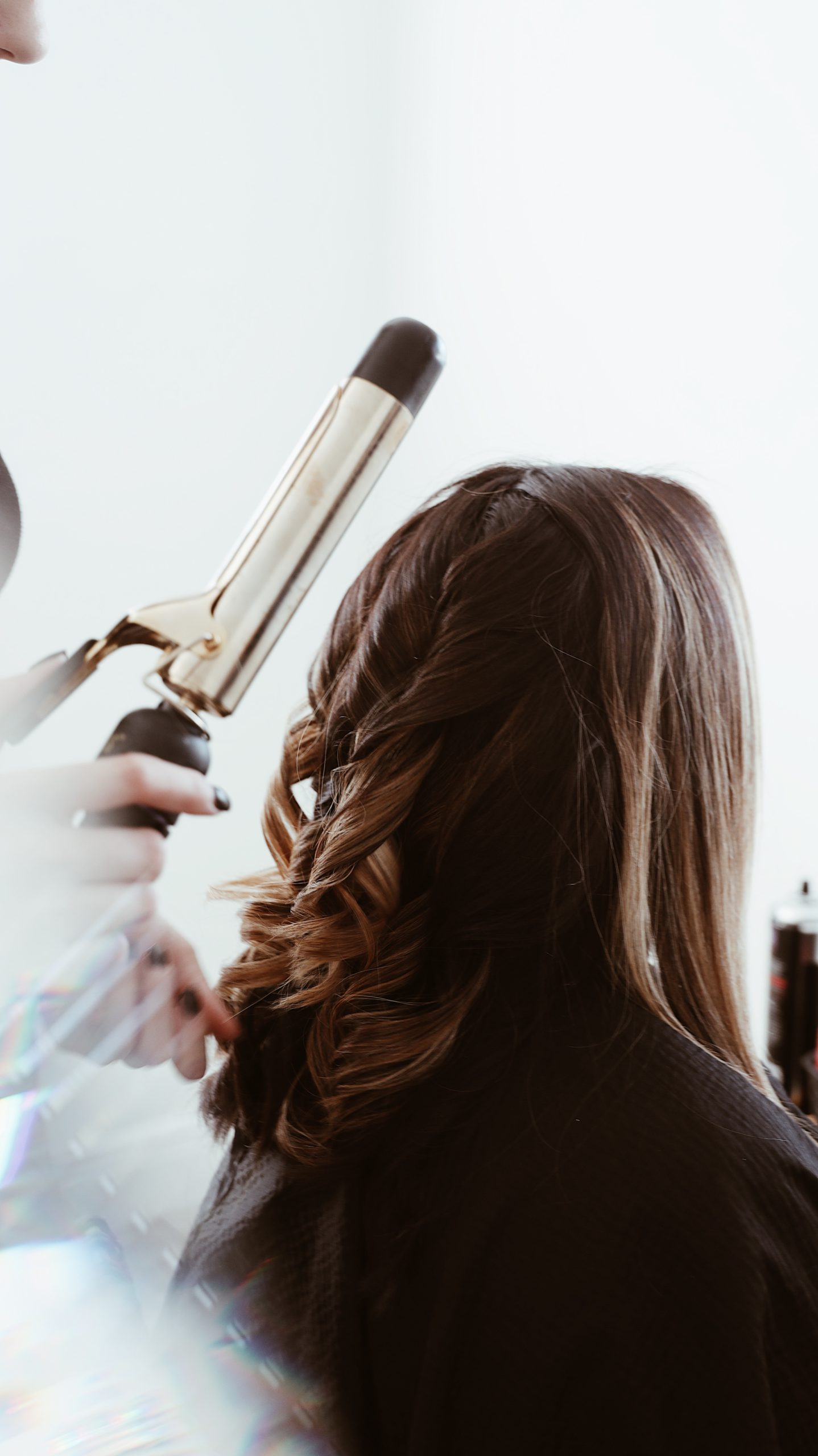 A curling iron behind a brunette woman on a white background.
